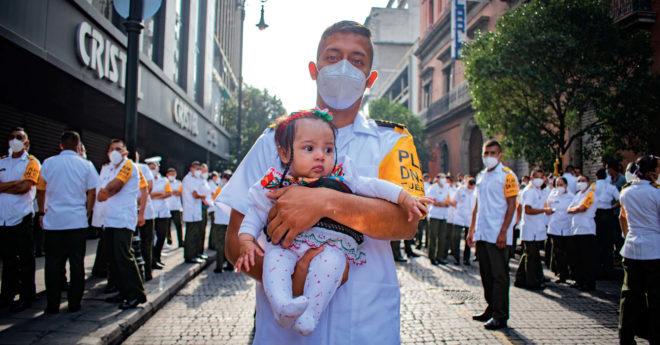 """""""Moreno"""", de la Escuela Militar de Clase de Sanidad, carga a su bebé de 5 meses antes de presentarse a desfilar en el Zócalo"""